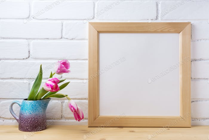 Wooden square frame mockup with pink tulip in purple blue vase