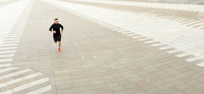Strong athletic man sprinter running outdoors in city