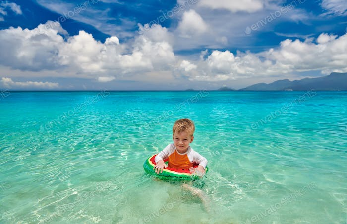 Toddler boy on beach swimming with inflatable ring