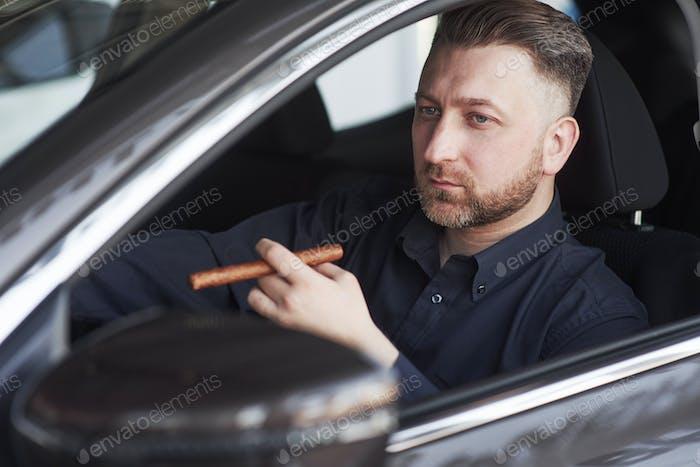 Mit Luxus-Zigarette Mann in offizieller Kleidung versucht sein neues Auto im Automobil-Salon