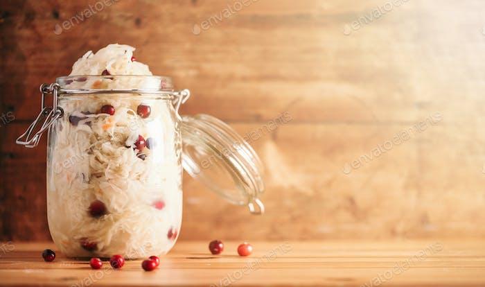 Fermentierter Kohl mit Preiselbeeren in Glasgefäß über Holzhintergrund. Probiotika Lebensmittelkonzept