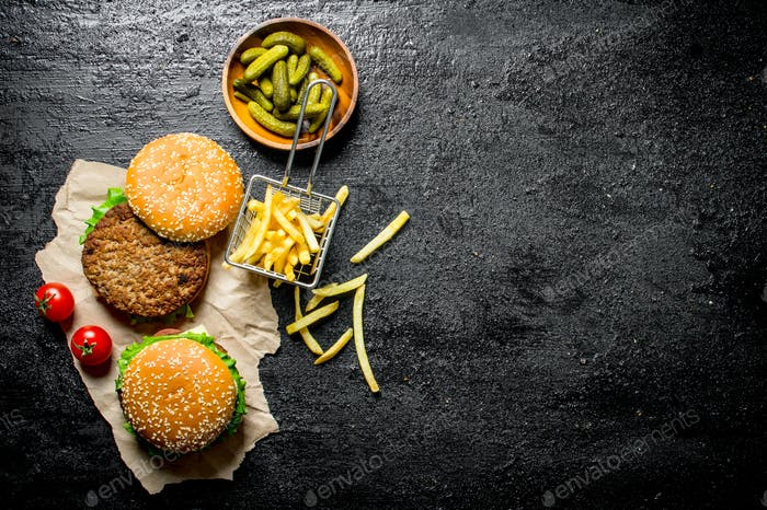Burgers on paper with French fries, pickles and tomatoes.