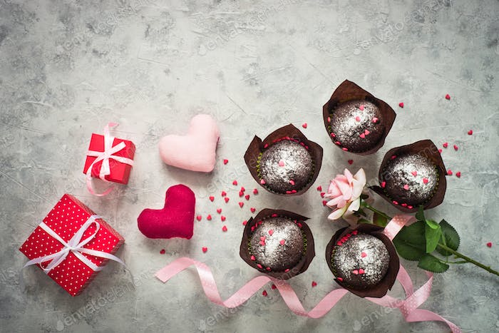Valentines day background. Chocolate cupcake, gift and flower.