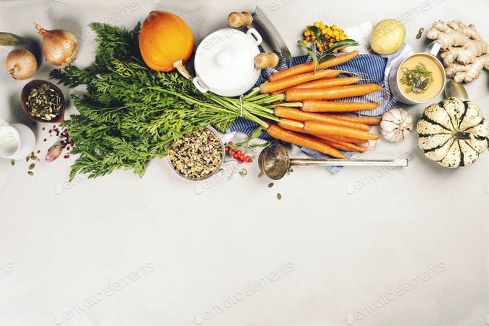 Fresh garden carrots, pumpkins, onions, apples and spices on rustic background