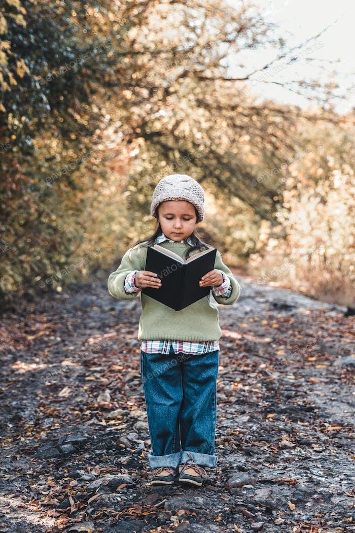 Kleines Mädchen liest ein Buch an einem Herbsttag. Bildung, Schule, Entwicklung