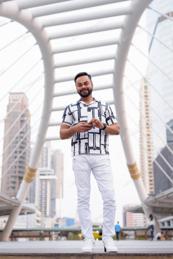 Full body shot of happy young bearded Indian man smiling in the city