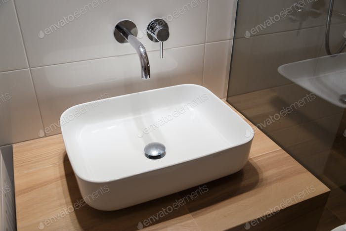 Close up of sink and faucet on wooden shelf in white bathroom interior