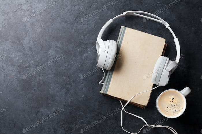 Audio book concept. Headphones, coffee and book