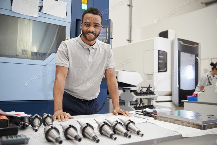 Portrait Of Male Engineer With CAD Drawings In Factory