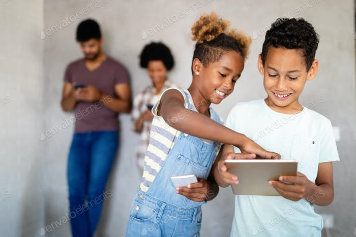 Happy children havig fun and using technology devices