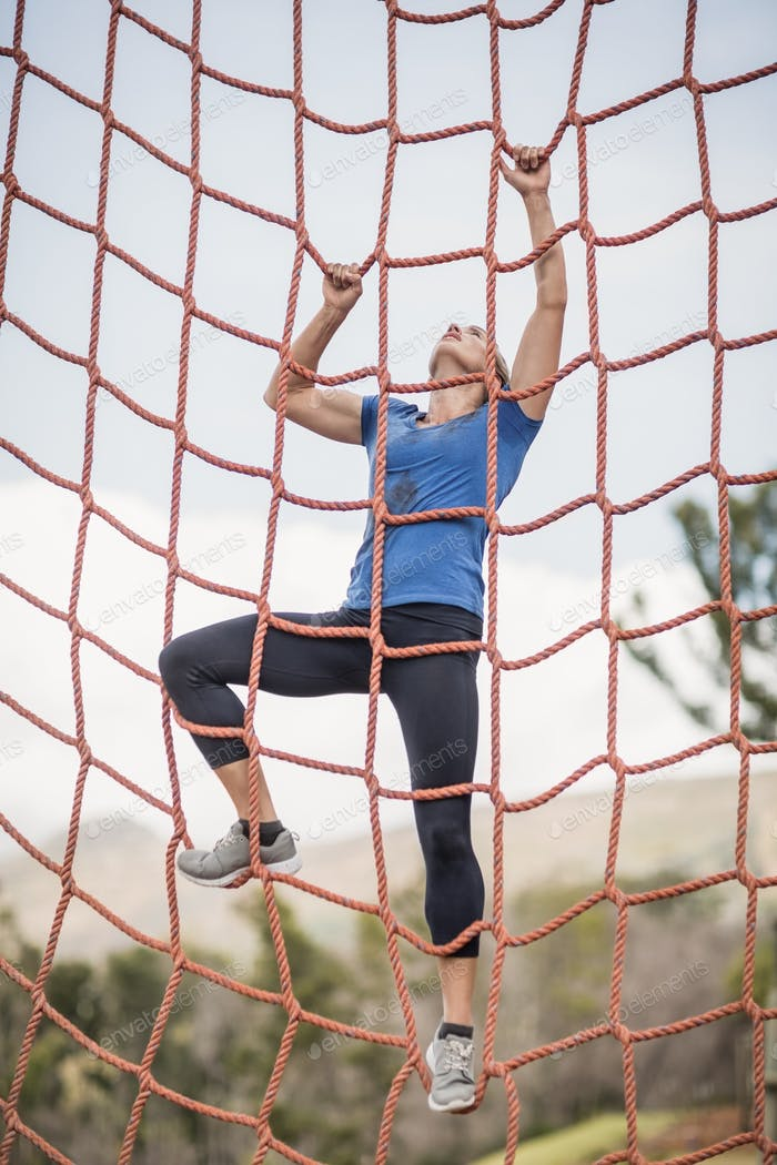 Fit woman climbing a net during obstacle course