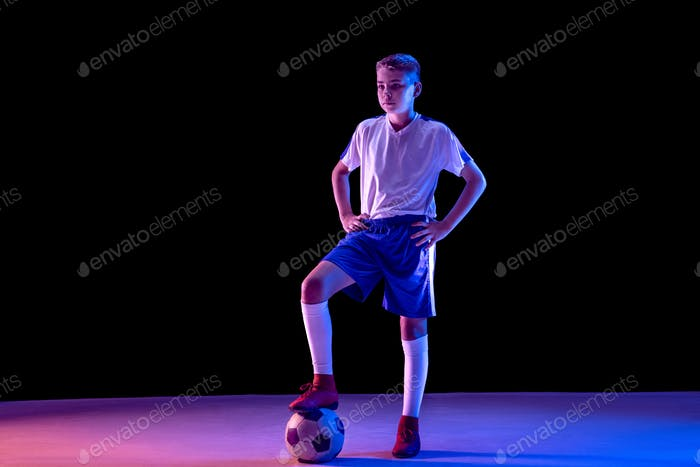 Young boy as a soccer or football player on dark studio background