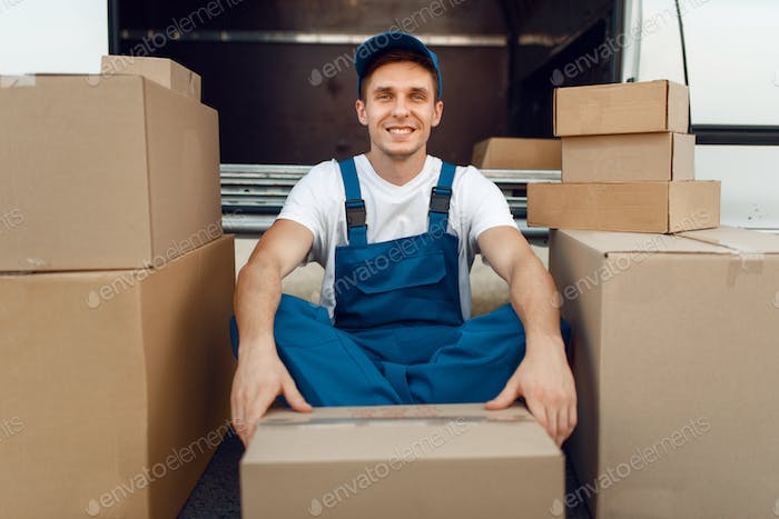 Deliveryman between parcels and carton boxes