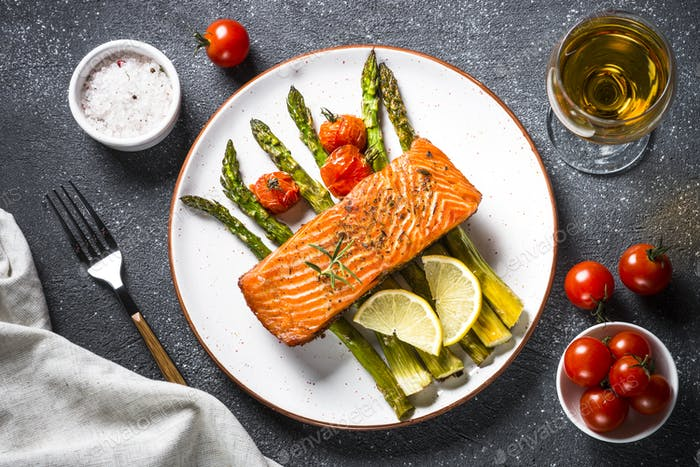 Gebackenes Lachsfischfilet mit Spargel und Tomate Draufsicht.