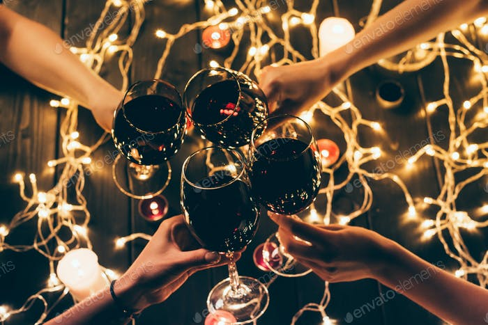 Cropped shot of four people clinking glasses with red wine over wooden table with fairylights