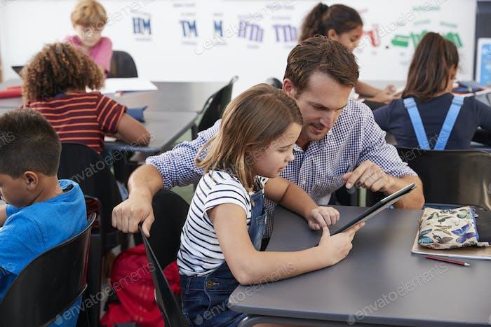 Lehrer und Schulmädchen mit Tablet-Computer in der Klasse