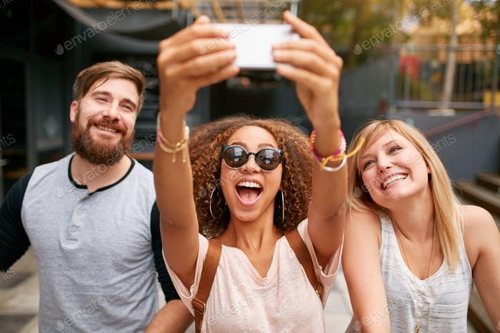 Gruppe von lächelnden Freunden nehmen selfie mit Smartphone