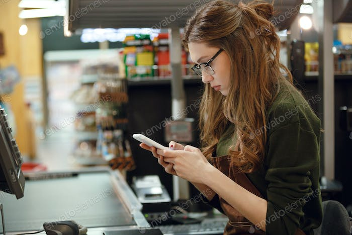 Cashier lady on workspace in supermarket shop using mobile