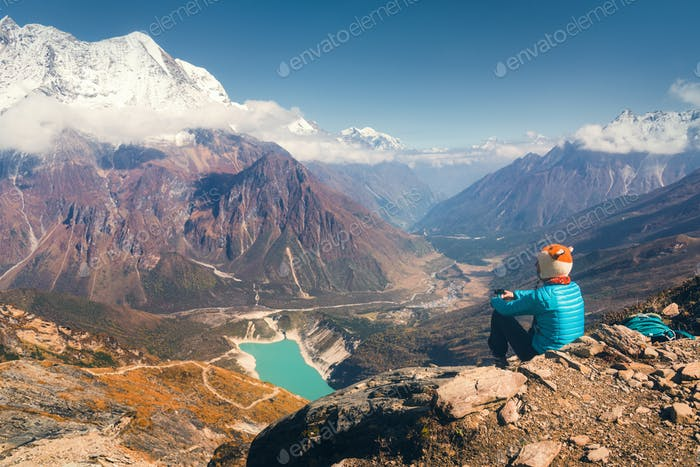 Sitting woman against beautiful lake and mountains