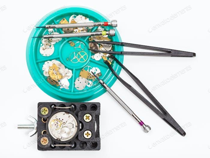 Draufsicht der Werkzeuge und Teile für die Reparatur der Uhr
