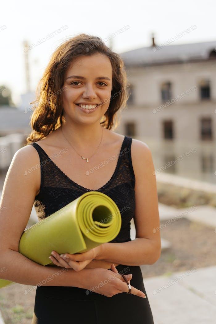 Woman holds yoga mat