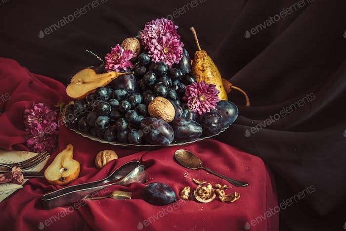 Die Obstschale mit Trauben und Pflaumen gegen eine kastanienrote Tischdecke