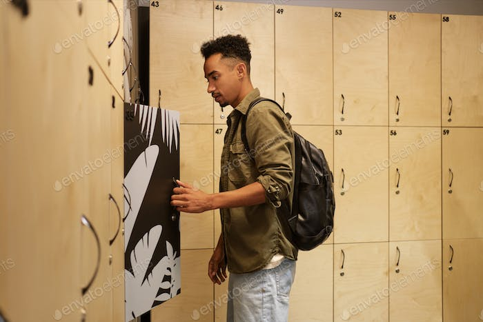 Young African American man with backpack leaving his things in locker in office cloakroom