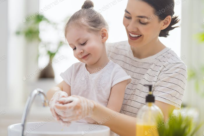 Mädchen und ihre Mutter waschen Hände