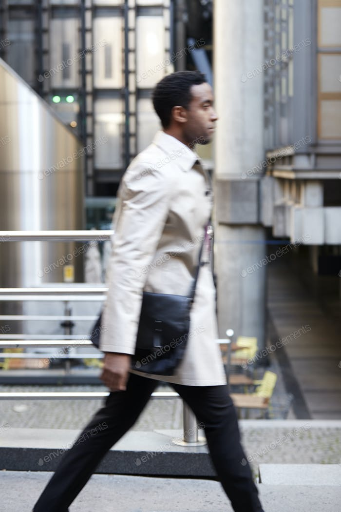 Side view of a young black businessman walking in a street in the city, London UK, motion blur