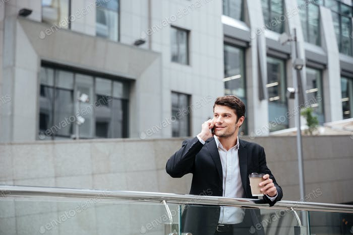 Happy young businessman talking on cell phone and drinking coffee
