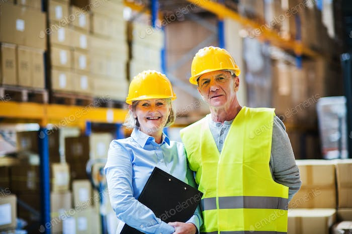 Senior woman manager and man worker standing in a warehouse.