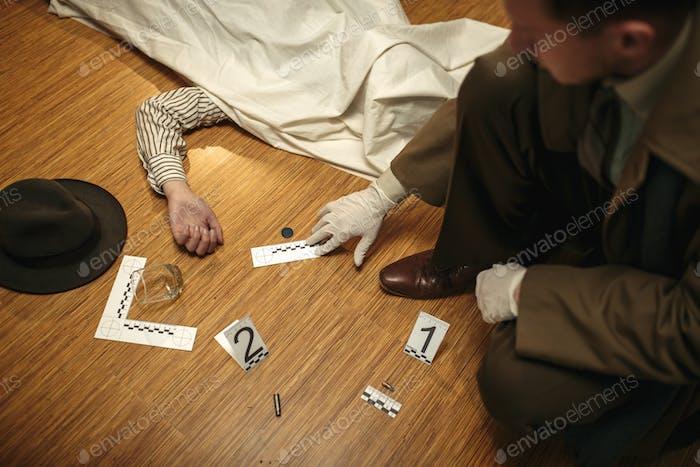 Detective in Handschuhen suchen Beweise, Tatort