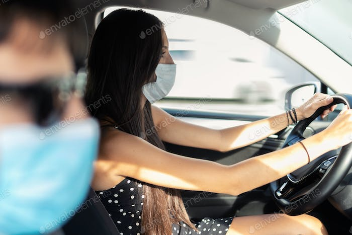 Beautiful young woman in face mask driving her car in the city.