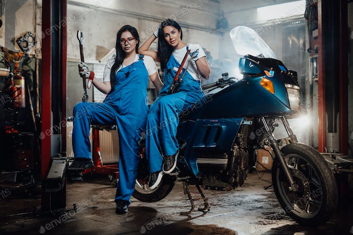 Two female mechanic posing next to a sportbike in authentic workshop garage