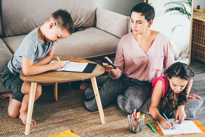 woman with mobile phone spends time with playful little boy with cat and teenager girl drawing