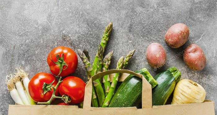 Different vegetables in paper bag on grey