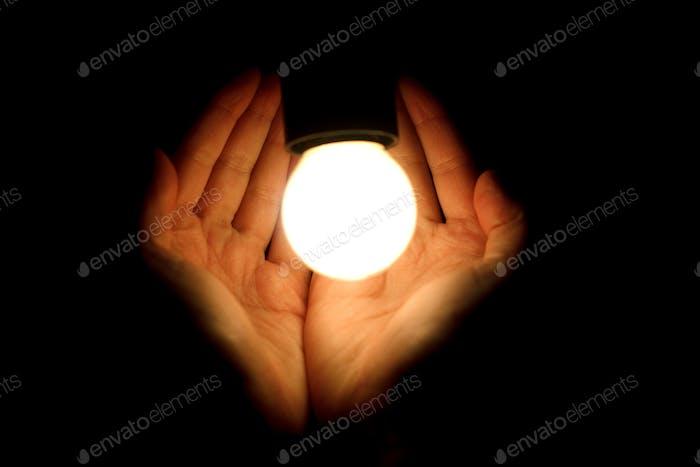 Glühbirne beim Menschen Hände auf schwarzem Hintergrund, Energieeinsparung und Innovationskonzept
