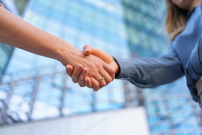 Woman hands shake on business building background