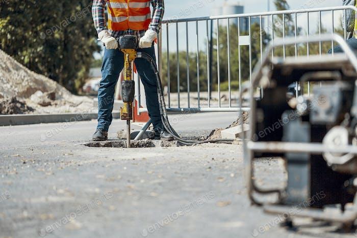 Ремесленник в форме с сверлом ремонт асфальта во время дорожных работ