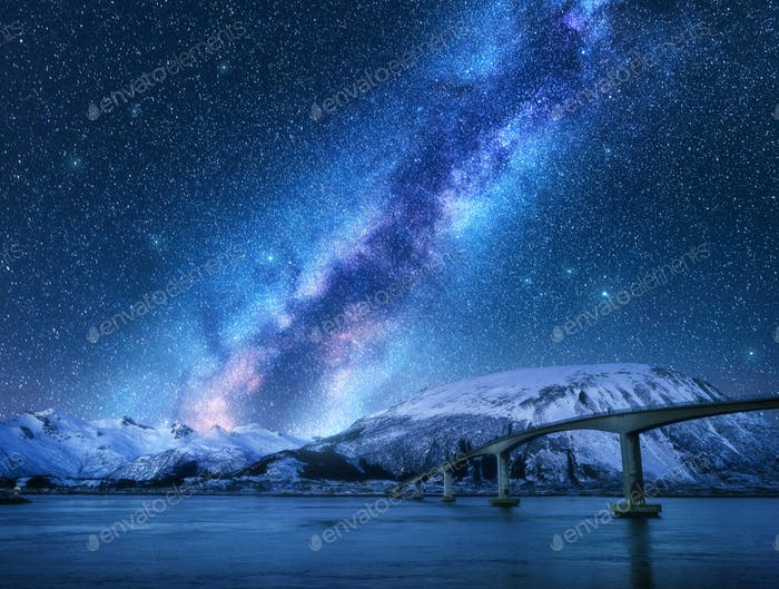 Bridge and starry sky with Milky Way over snow covered mountains