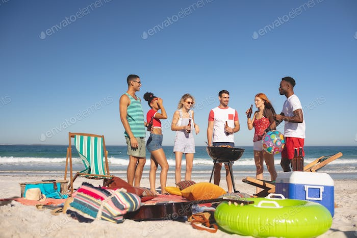 Front view of group of happy diverse friends having fun while preparing food on barbecue at beach