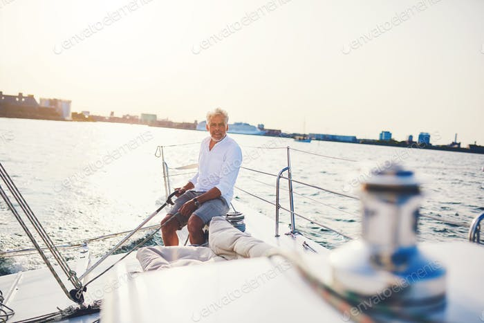 Mature man sailing his boat alone on the ocean