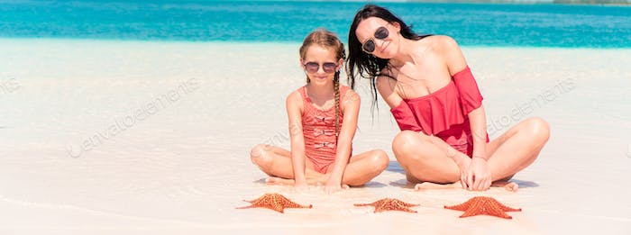 Mother and little daughter enjoying time at tropical beach