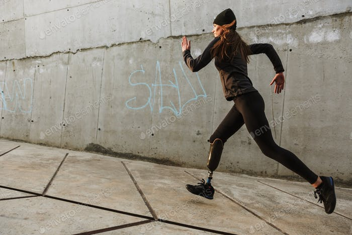 Portrait of disabled athlete woman with prosthetic leg in tracks