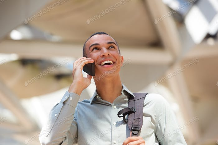 happy young businessman talking on cellphone and looking up