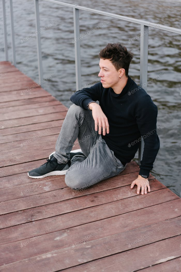 Young man sitting on a wooden pier