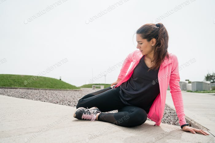 Athletic woman stretching legs before exercise.