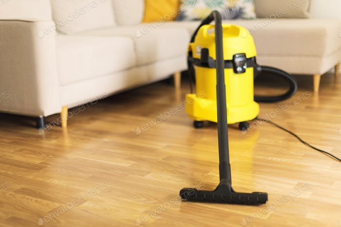 Woman in protective gloves cleaning the living room with yellow vacuum cleaner. Copy space. Clean
