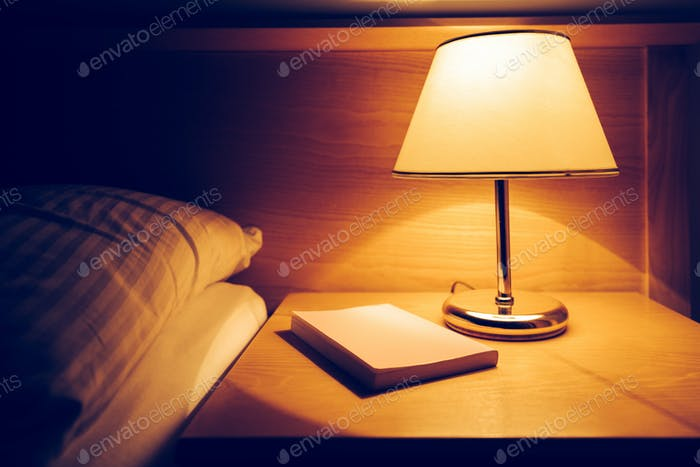 Book and lamp on night table in hotel room