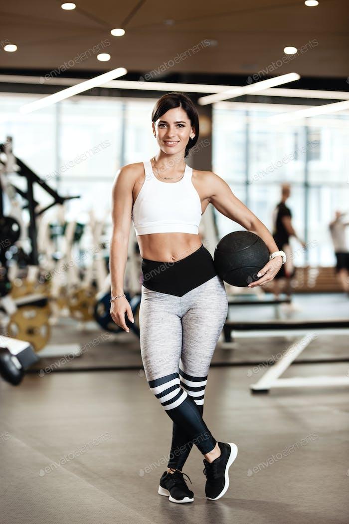 Schlanke Brünette Mädchen in einer Sportbekleidung gekleidet steht mit schweren Fitnessball in ihren Händen in